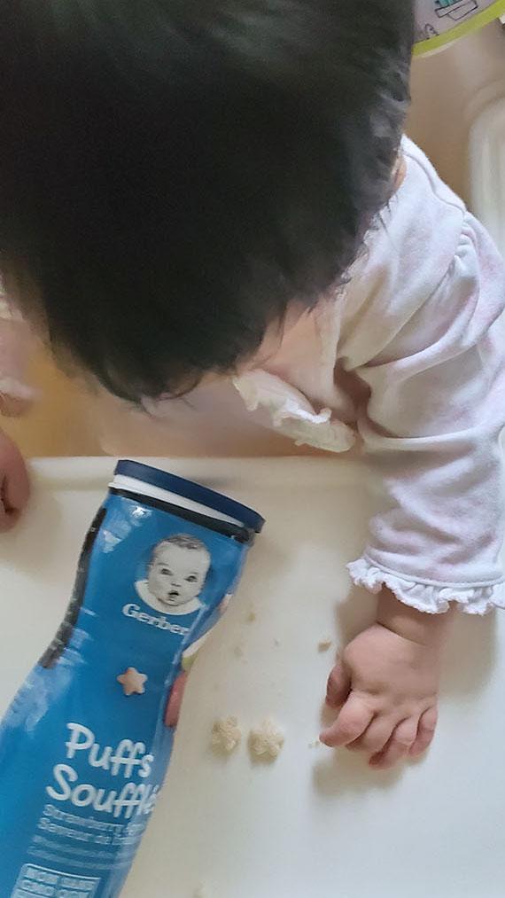 Baby grabbing Gerber puff cereal snacks.