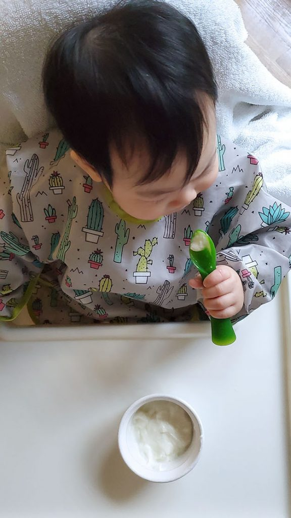Baby feeding herself yogurt with a spoon.