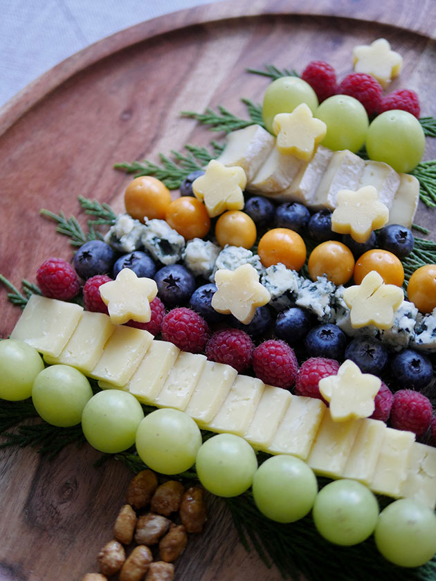 Close up of a wooden cheeseboard with fruits, nuts and cheeses laid out in a pattern that resembles a Christmas tree.