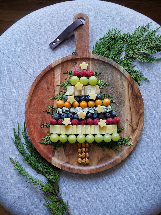 A wooden cheeseboard with fruits, nuts and cheeses laid out in a pattern that resembles a Christmas tree.