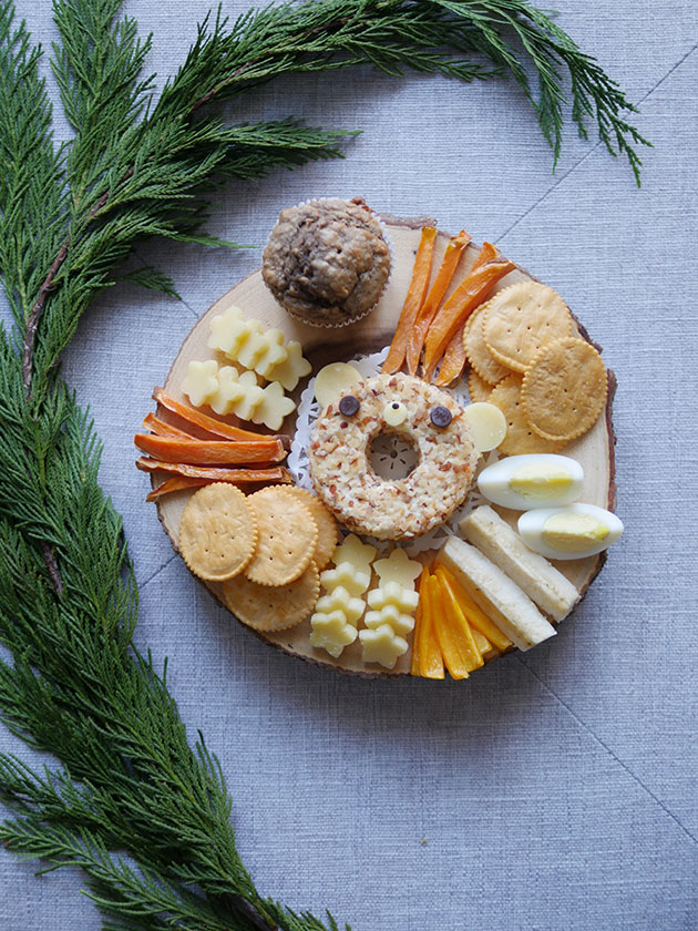 A round wooden cheeseboard holding crackers, muffins, yam fries, eggs and peppers. In the center is a ring of cheese that resembles a bear shape.