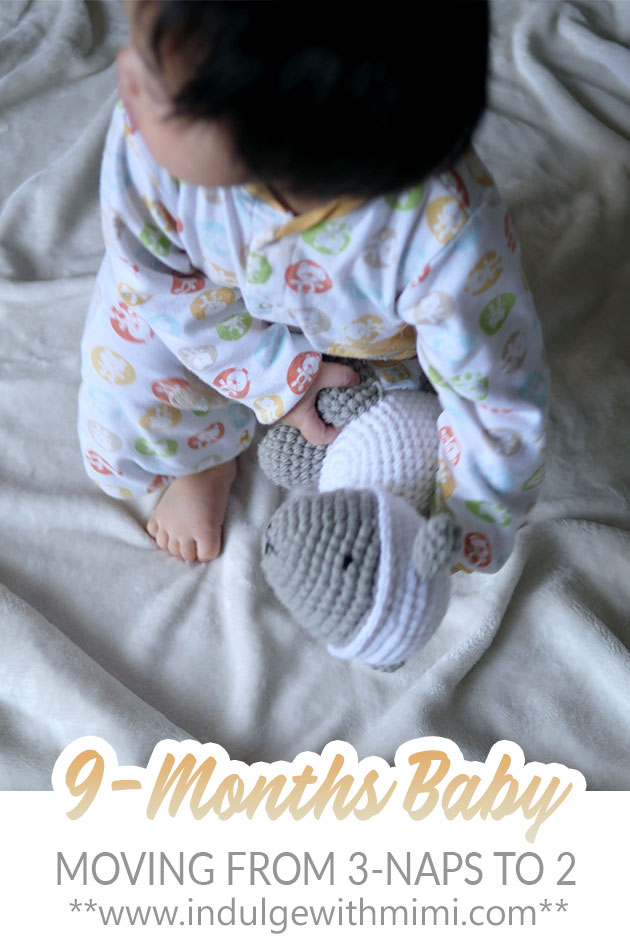 Baby on bed holding onto lamb doll.