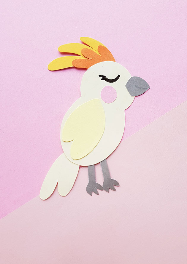 Cockatoo paper craft shown against pink background.
