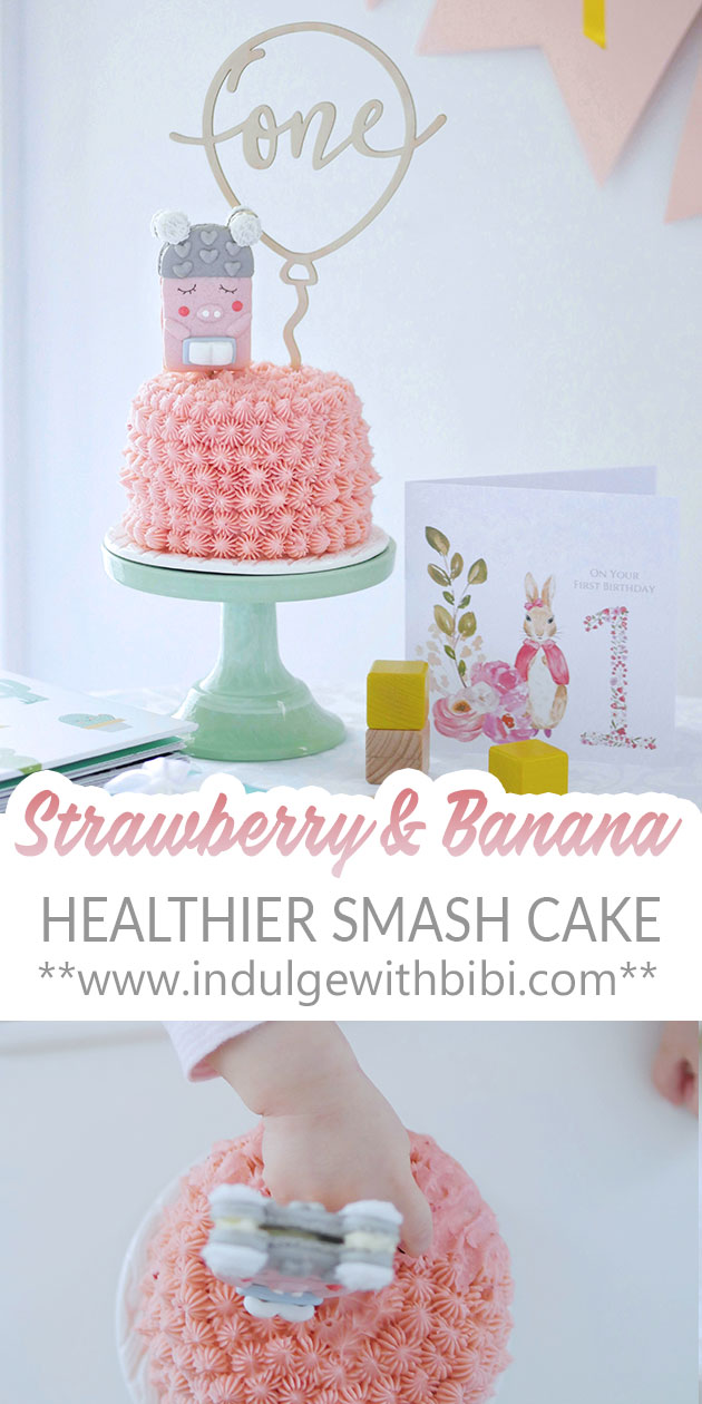 Baby with hand in pink smash cake.