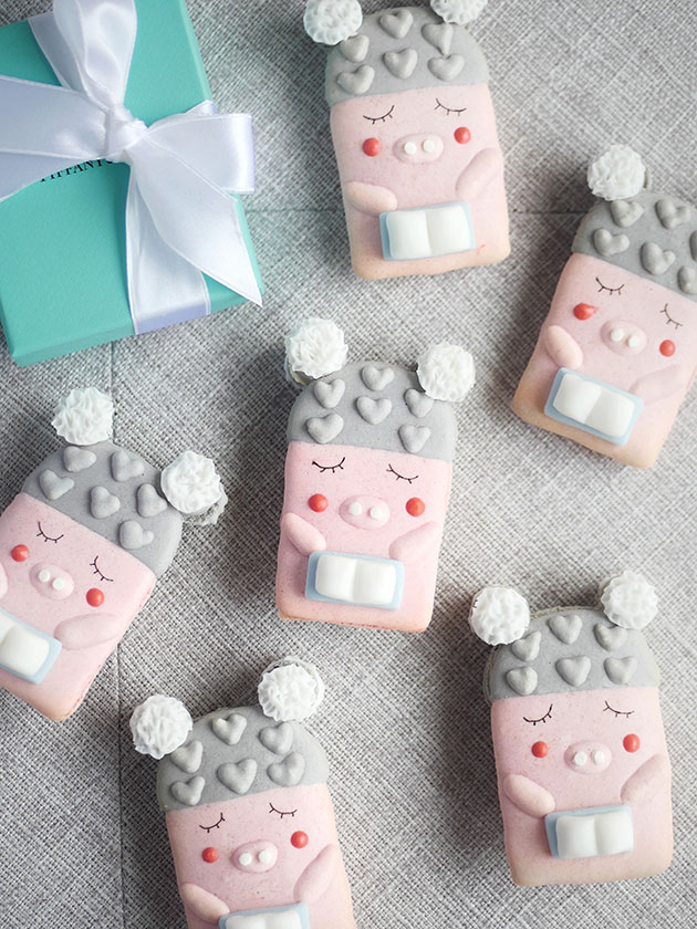 Pink macaron piggies holding onto a book.