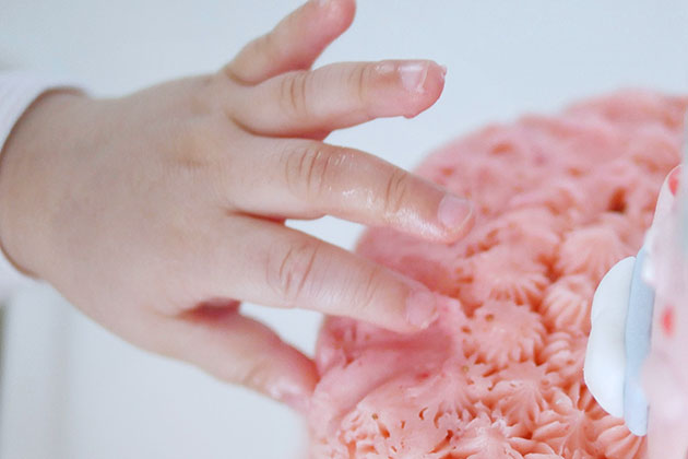 Baby's fingers on the pink frosting of the mini cake.