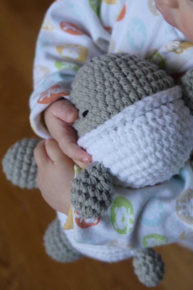 Close up of baby hands holding onto a crochet lamb.