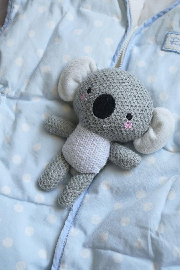 Close up of koala stuffy with baby sleep sack.