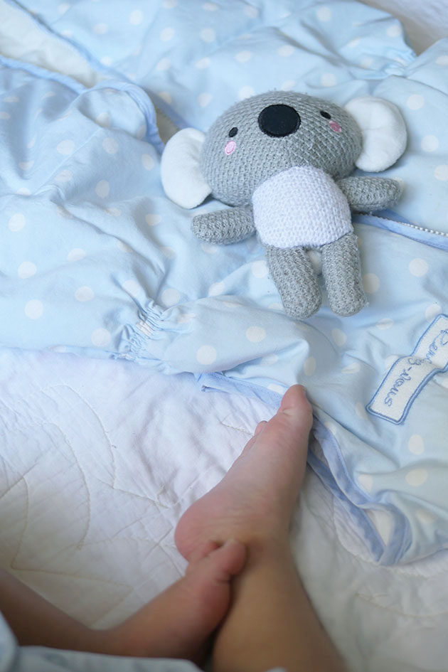 Baby feet with sleep sack and koala bear.