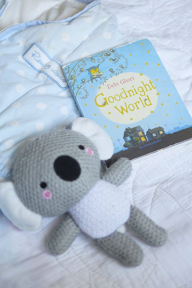 Koala on the bed with good night book for baby.