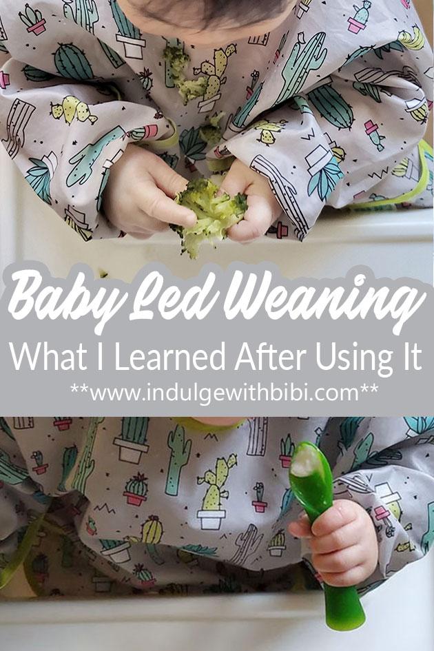 Baby feeding herself broccoli.
