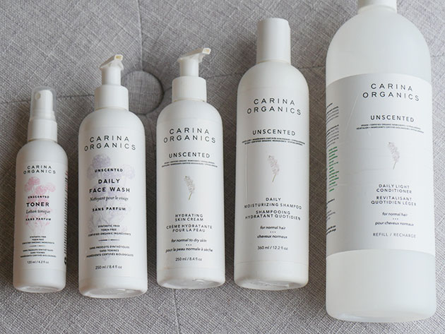 A collection of clean white bottles of Carina Organics natural body care products.
