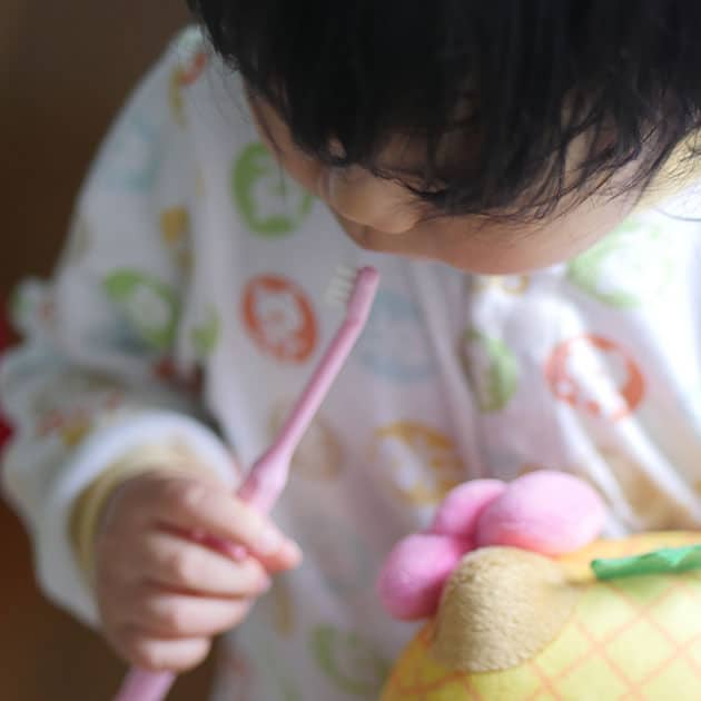 Baby brushing teeth as part of a realistic bedtime routine.