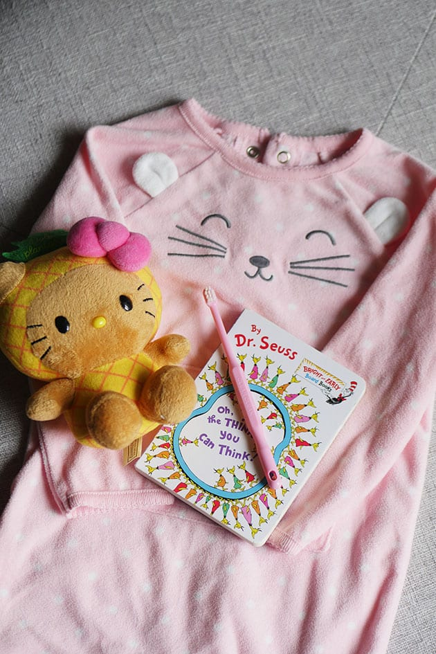 Pink pajamas with a hello kitty stuffie and toothbrush and book.