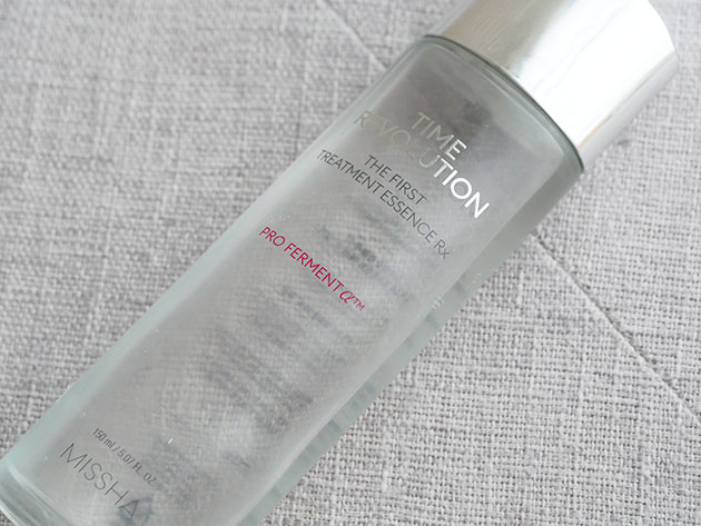 A glass bottle filled with clear face essence.