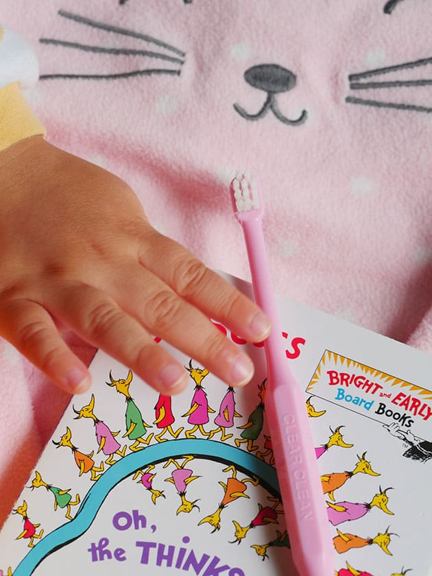 Baby hands reaching for toothbrush, part of baby's realistic bedtime routine.