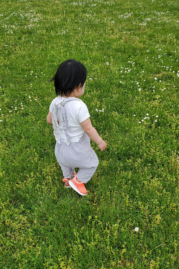 Baby exercising, running in the grass.