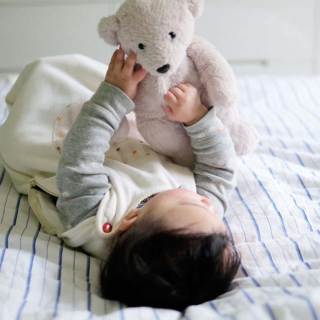 Baby self-soothing to sleep on the bed with a teddy bear.