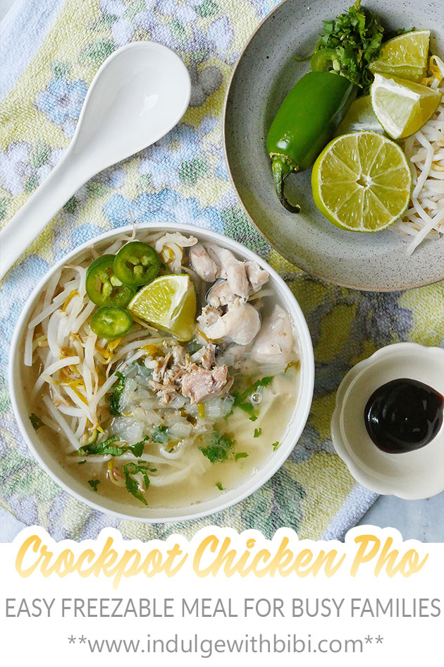 A bowl of crockpot chicken pho noodles shown with another plate filled with condiments like lime, jalapenos, bean sprouts etc.