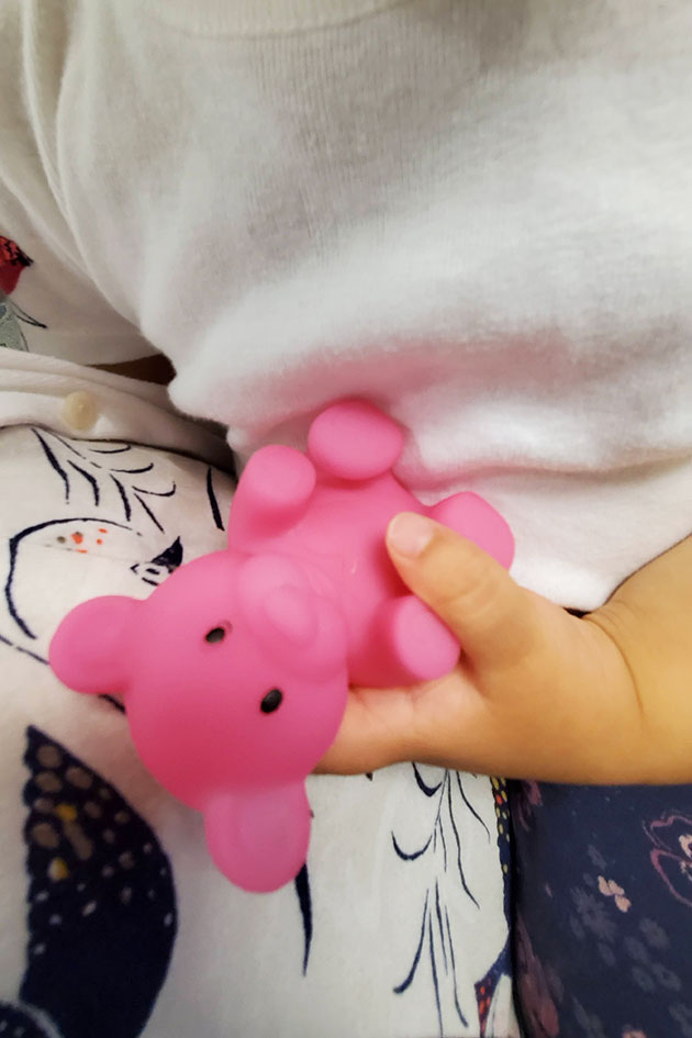 Baby holding onto a dental gift - a plastic bear.
