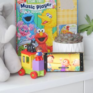 screen showing baby tv program is shown with books and legos.