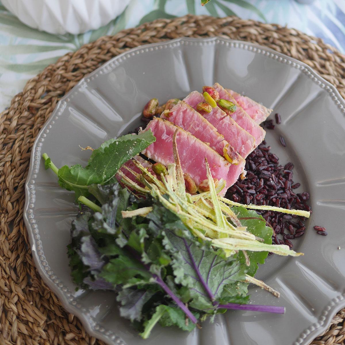 Ahi tuna steak on a plate with fresh vegetables.