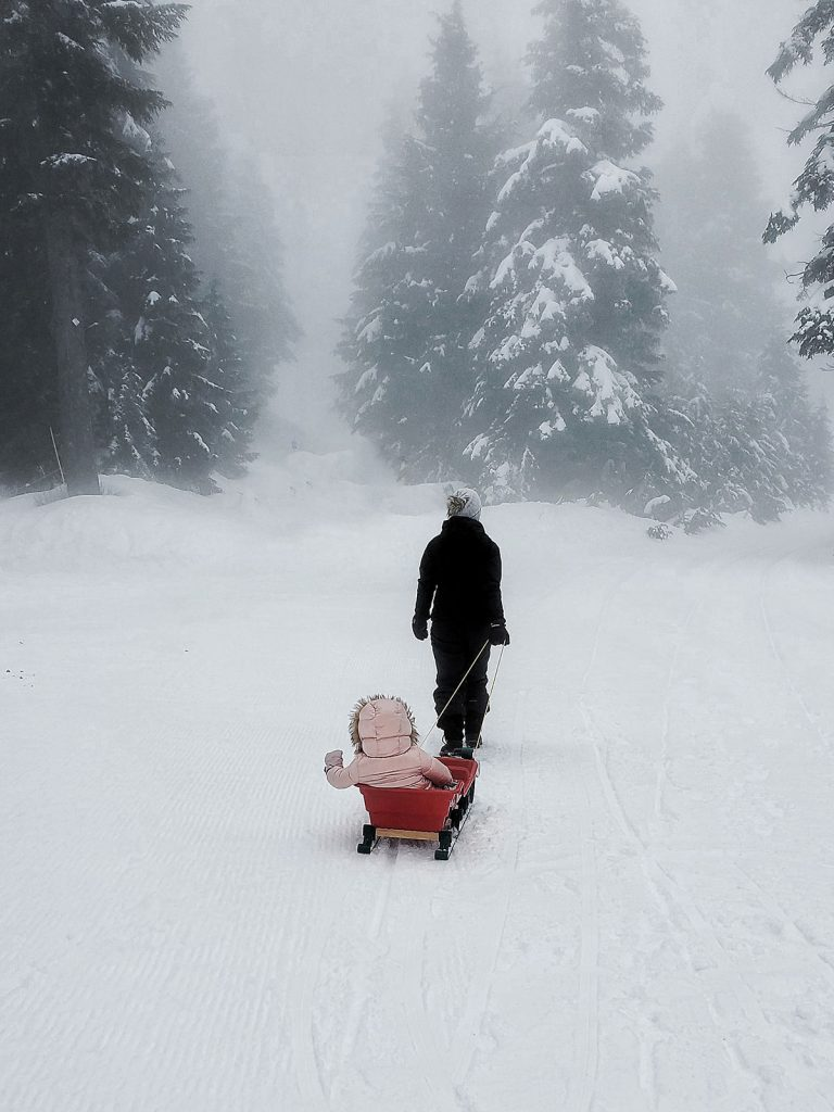 Mother pulling baby in a sled in snow.