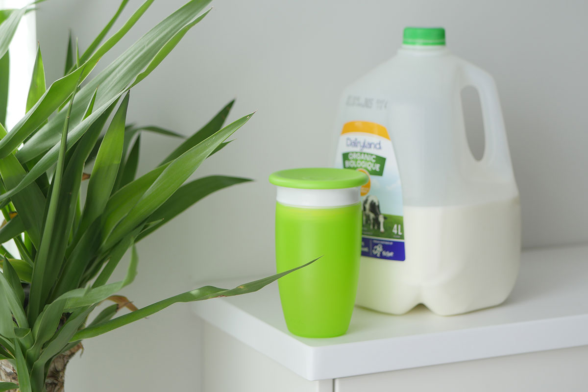 A jug of whole fat cows milk on a counter.