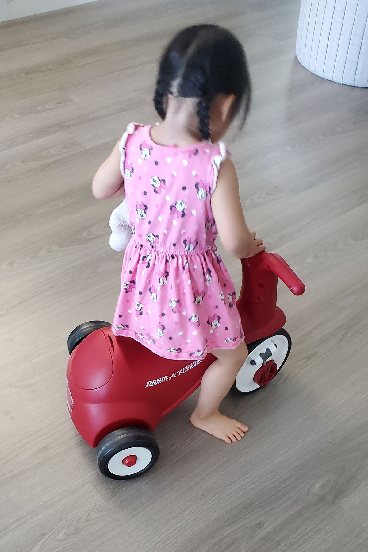 Baby toddler playing independently on a red bike.