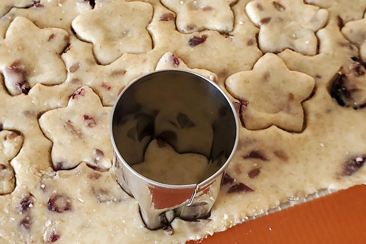 Small cookie cutter cutting out sourdough dough.